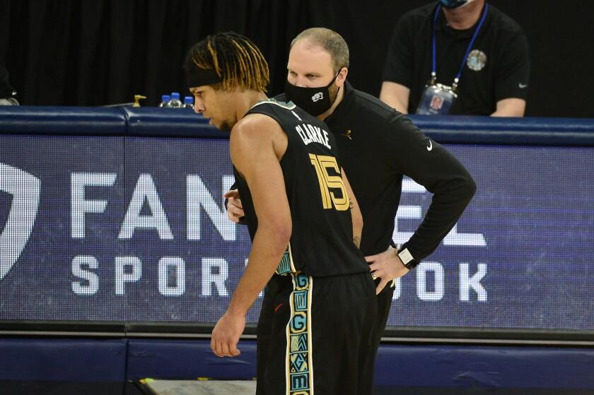 El entrenador de los Grizzlies de Memphis Taylor Jenkins, derecha, habla con su jugador Brandon Clarke.