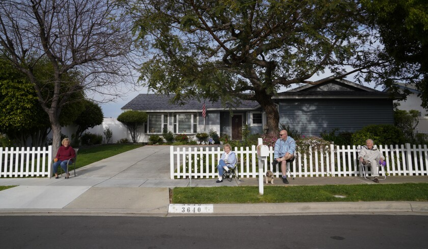 Kelly Gaglione, left, and her next-door neighbors, Suzanne Stelmach, Dave Stelmach and Allan Stelmach, enjoy sitting at the sidewalk in front of their home in Carlsbad. The neighbors on Trieste Drive gather once a week at the end of their driveway to enjoy a cocktail and a few laughs.