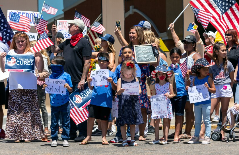 People rally May 13 in support of opening small businesses outside the Metroflex Gym in Oceanside.