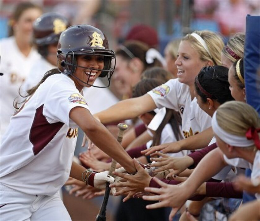 ASU's Alix Johnson slaps hands with her teammates as she runs along the dugout after scoring against Florida in the second inning of a Women's College World Series championship series game.