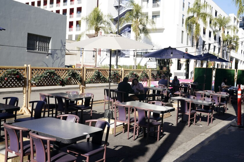 FILE - In this Dec. 4, 2020, file photo, empty tables are seen outside of a restaurant set up for outdoor dining in Burbank, Calif. Five California legislative assembly members dined together outdoors Monday, Dec. 8, 2020, despite surging coronavirus case levels that have triggered stay at home orders for much of the state's population. State rules are silent as to how many households can dine together outdoors at restaurants, but health officials have implored people to limit outside gatherings to no more than three households.(AP Photo/Marcio Jose Sanchez, File)