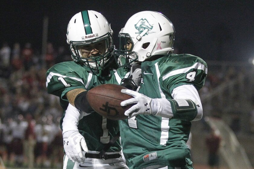 Isaiah Paopao (right) and Oceanside teammate Johnny Arzola celebrate Paopao's 10-yard touchdown catch on a halfback pass in the first quarter of the No. 1-ranked Pirates' win over No. 2 Mission Hills.