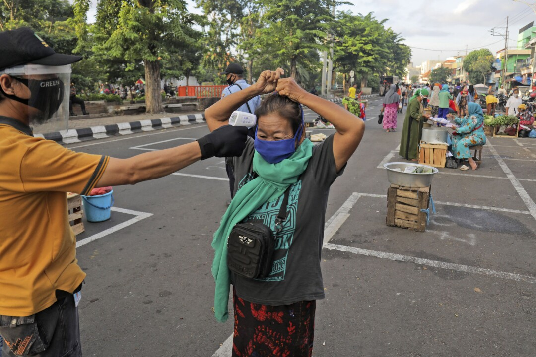 A city official takes the temperature of a vendor at a market in Surabaya, Indonesia.