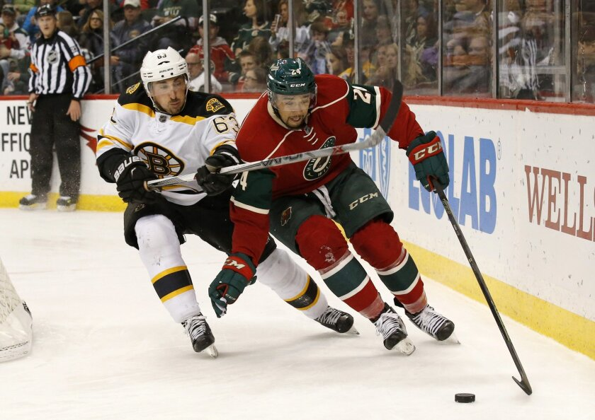 Boston Bruins left wing Brad Marchand (63) and Minnesota Wild defenseman Matt Dumba (24) chase the puck during the second period of an NHL hockey game in St. Paul, Minn., Saturday, Feb. 13, 2016. (AP Photo/Ann Heisenfelt)