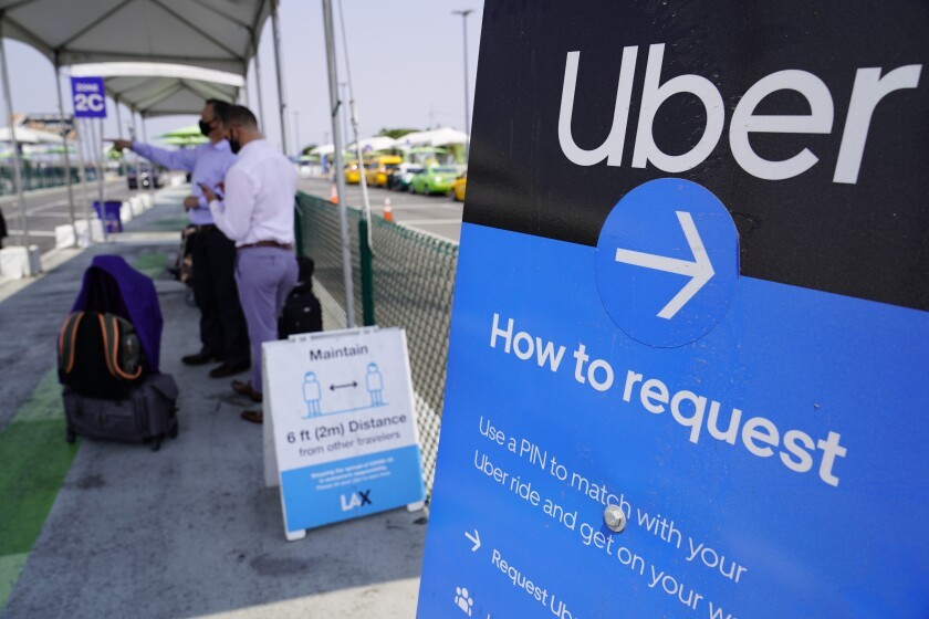 FILE - In this Aug. 20, 2020, file photo travelers request an Uber ride at Los Angeles International Airport's LAX-it pick up terminal. A California ballot measure that would exempt Uber, Lyft and other app-based delivery drivers from being classified as company employees eligible for benefits and job protections led Tuesday, Nov. 3, 2020, in early vote counts. (AP Photo/Damian Dovarganes, File)