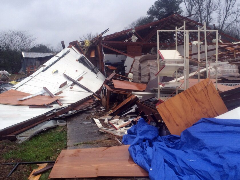 Area residents survey damage to a business off Mississippi Highway 18 in Sylverana, Miss., Monday, Feb. 15, 2016, after severe weather affected south Mississippi. No injuries were reported in the storm. Officials are investigating reports of at least two possible tornadoes that accompanied a line o