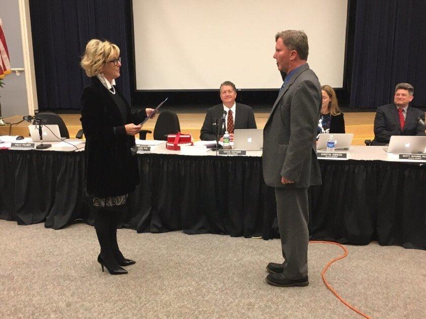 New board member Stephen Cochrane takes the oath of office.