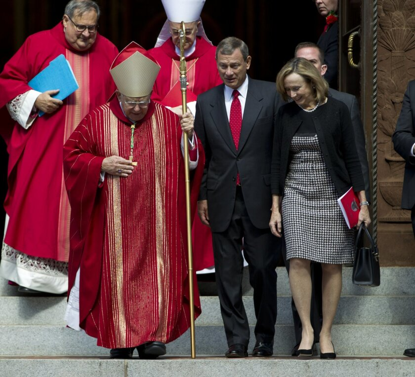 Bishop of Arlington, Rev. Paul Loverde, talks with U.S. Supreme Court Chief Justice John Roberts, center, and his wife Jane Marie, as they leave the Cathedral of St. Matthew the Apostle after the annual Red Mass for Supreme Court justices in Washington, Sunday, Oct. 5, 2014. The new Supreme Court term starts Monday. (AP Photo/Jose Luis Magana)