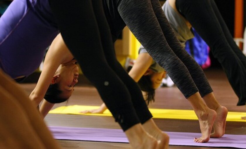 Customers participate in a yoga class at the Lululemon store at South Coast Plaza in Costa Mesa in this file photo.