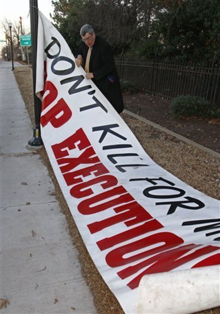 Attorney James T. Rowan unfurls a banner against the death penalty outside the governor's mansion in Oklahoma City, Thursday, Jan. 6, 2011. Billy Don Alverson, 39, has been executed, Thursday, for the death of a Tulsa convenience store worker found brutally beaten with a baseball bat almost 16 years ago. (AP Photo/Sue Ogrocki)