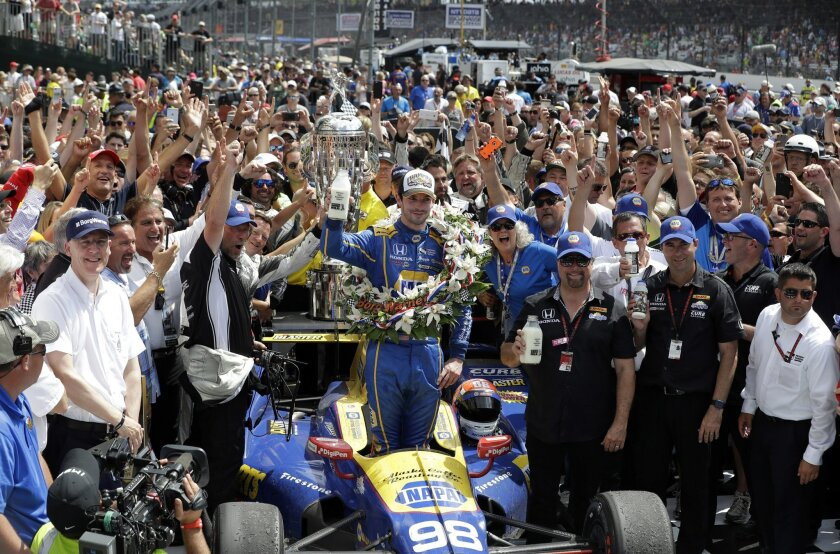 Alexander Rossi, center, celebrates after winning the 100th running of the Indianapolis 500 auto race at Indianapolis Motor Speedway in Indianapolis, Sunday, May 29, 2016. (AP Photo/Darron Cummings)