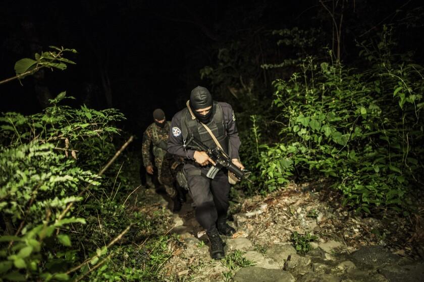 En esta imagen del 27 de mayo de 2015, un agente de policía y un soldado patrullan una zona rural tras violentos enfrentamientos entre policía y pandilleros.