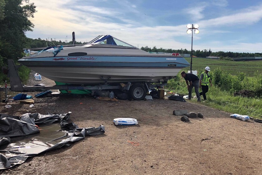 Security guards check on protesters under a boat blocking an entrance to an Enbridge Line 3 pumping station near Park Rapids, in northern Minnesota, Tuesday June 8, 2021. (AP Photo/Dave Kolpack)