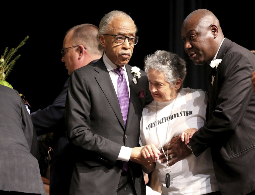 Rev. Al Sharpton, left, and attorney Benjamin Crump, right, escort Rebecca Payne to view her grandson's casket during the funeral service for 17-year-old Hunter Brittain, on Tuesday, July 6, 2021, at the Beebe High Schools Auditorium in Beebe, Ark. Brittain was shot by a Lonoke County Sheriff's Deputy during a traffic stop on June 23. (Tommy Metthe/The Arkansas Democrat-Gazette via AP)