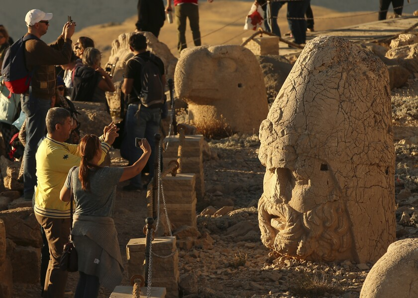 In this Monday, Sept. 23, 2019 photo, tourists take photos at the archaeological site of Mount Nemrut in Adiyaman, southeastern Turkey, a UNESCO World Heritage Site since 1987. Perched at an altitude of 2,150 meters, the statues are part of a temple and tomb complex that King Antiochus I, of the ancient Commagene kingdom built as a monument to himself. The ancient site, which includes giant 10-meter high, seated statues of King Antiochus I surrounded by ancient Gods, including Zeus and Apollo, was discovered in 1881 by a German engineer. (AP Photo/Emrah Gurel)