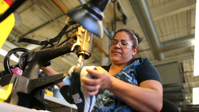 Eddy Maria Taveras uses a Singer sewing machine to repair a running shoe at the New Balance factory in Lawrence, Mass.
