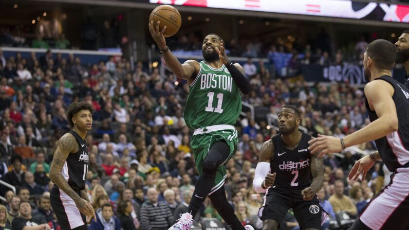 Boston Celtics guard Kyrie Irving (11) shoots between Washington Wizards forward Kelly Oubre Jr. (12), guard John Wall (2), and guard Austin Rivers, right, during the second half.