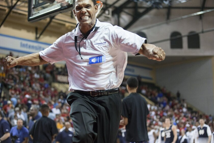 FILE - In this Nov. 26, 2015, file photo, Monmouth coach King Rice leaps as he runs off the court after Monmouth defeated Notre Dame 70-68 in an NCAA college basketball game, in Orlando, Fla. At this time of year college basketball coaches often sound like political candidates looking for votes as