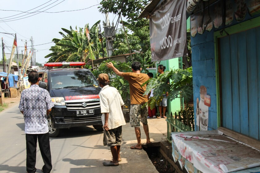 Three people gather in front of an ambulance.