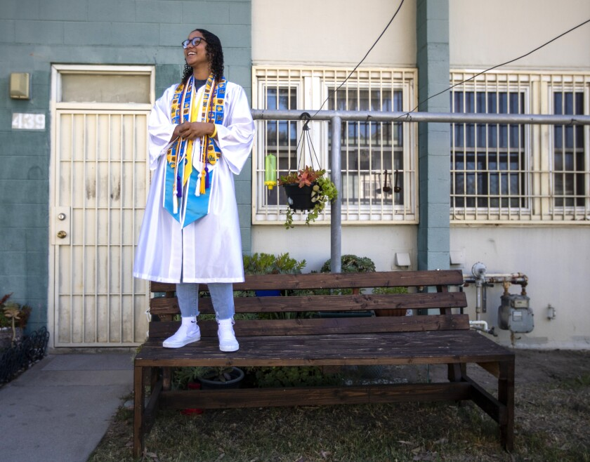 Pilar Diaz Bombino stands on a bench in her graduation gown