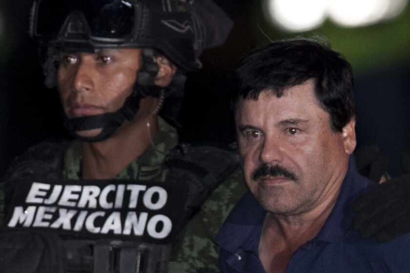 """Mexican drug lord Joaquin """"El Chapo"""" Guzman, right, is escorted to a helicopter in Mexico City on his way back to prison Friday."""