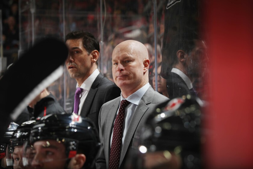 Devils coach John Hynes stands behind the bench during a game against the Penguins on Feb. 19.