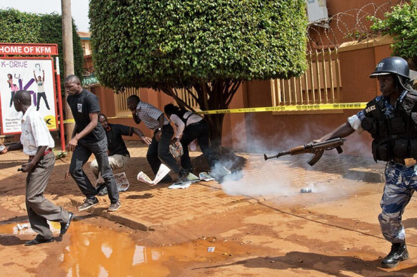 Ugandan police in Kampala on Tuesday use tear gas to disperse protesting journalists outside the Daily Monitor and Red Pepper newspapers, which were closed May 20 by police.