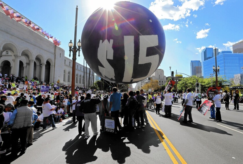 Protesters call for a higher minimum wage in Los Angeles in November. The wage will rise in California, New York and several other states on Friday.