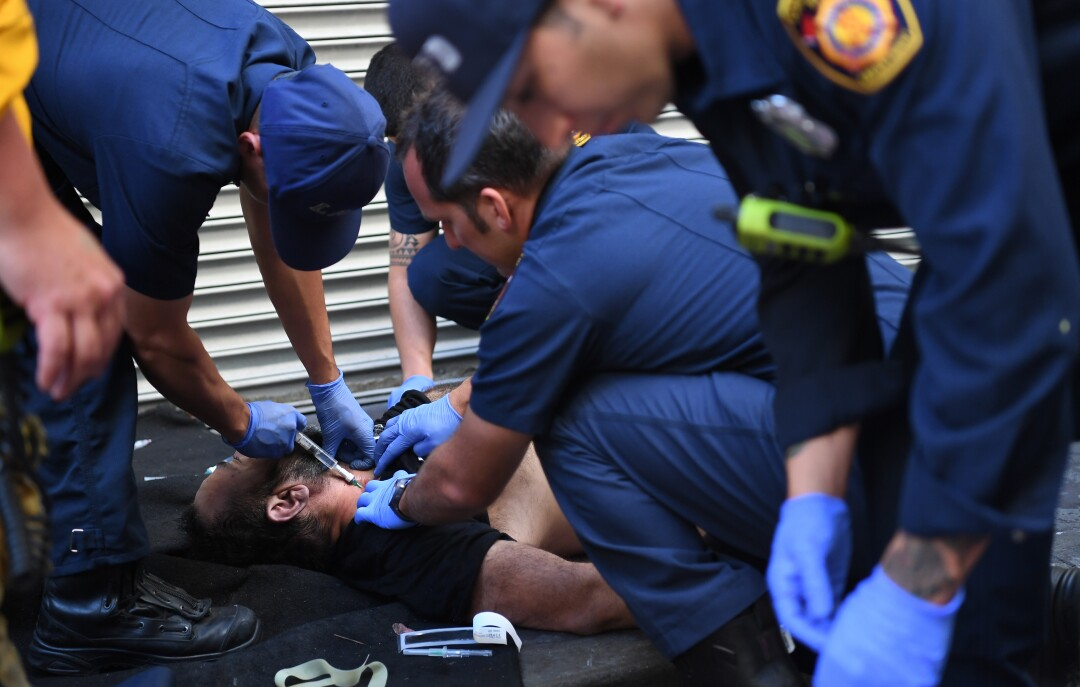 Los Angeles firefighters inject naloxone into the neck of an overdose patient