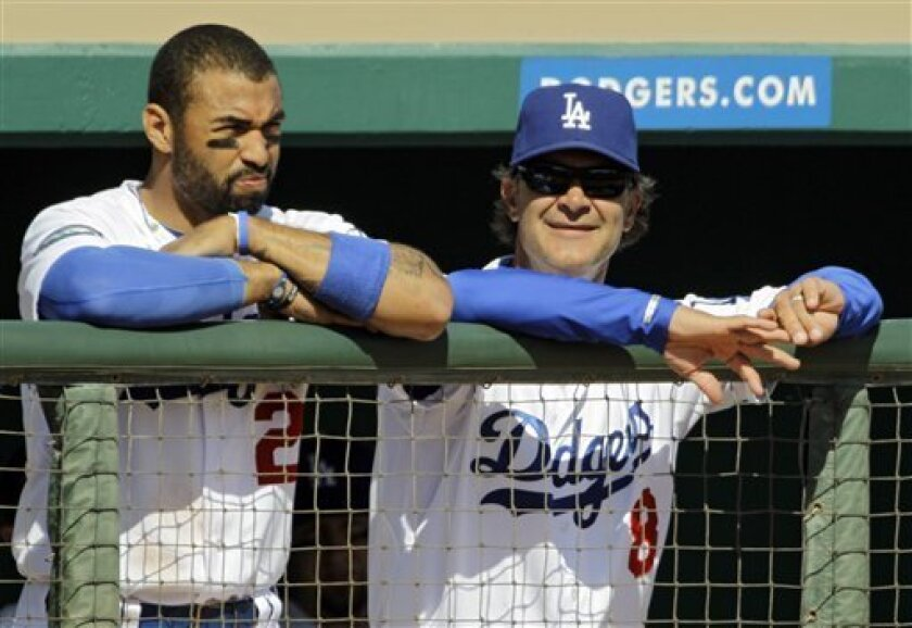 Los Angeles Dodgers' Matt Kemp, left, watches from the dugout with manager Don Mattingly during a spring training baseball game against the Oakland Athletics, Thursday, March 8, 2012, in Glendale, Ariz. (AP Photo/Mark Duncan)