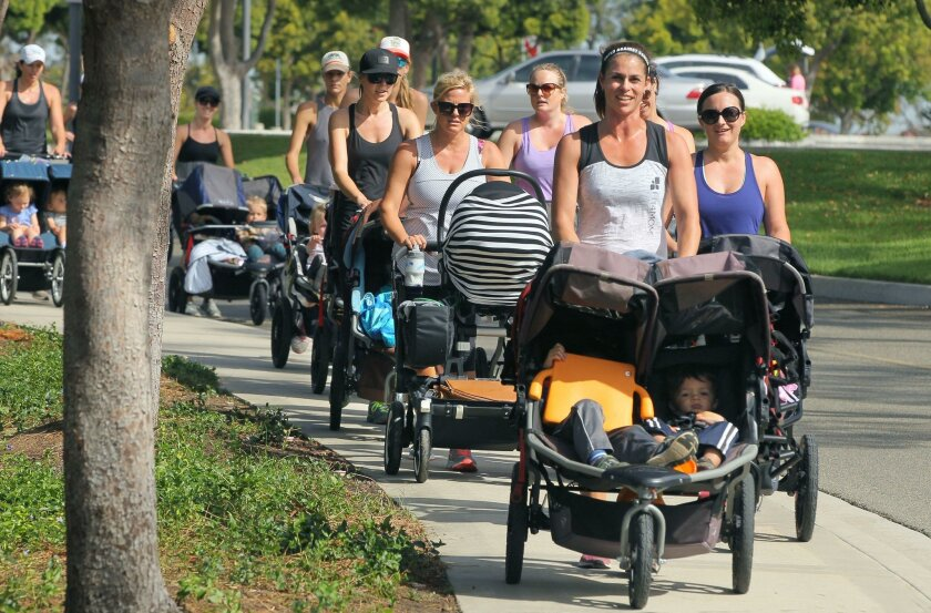 Fitness instructor Ann Ross (front) leads a morning Fit4Mom class at Carlsbad's Poinsettia Park.