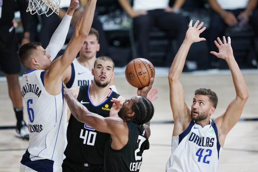 Clippers' Kawhi Leonard drives between Dallas Mavericks' Kristaps Porzingis and Maxi Kleber.