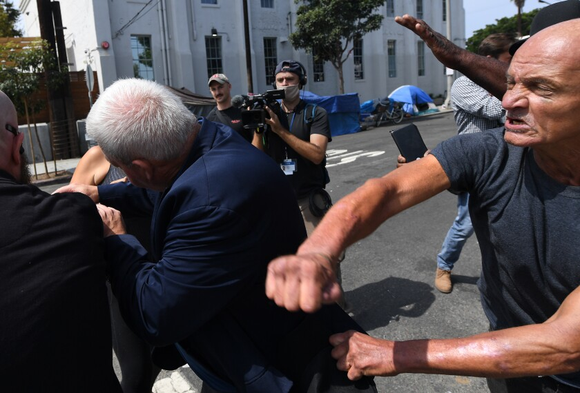 A homeless man takes a swing at a staff member for Larry Elder