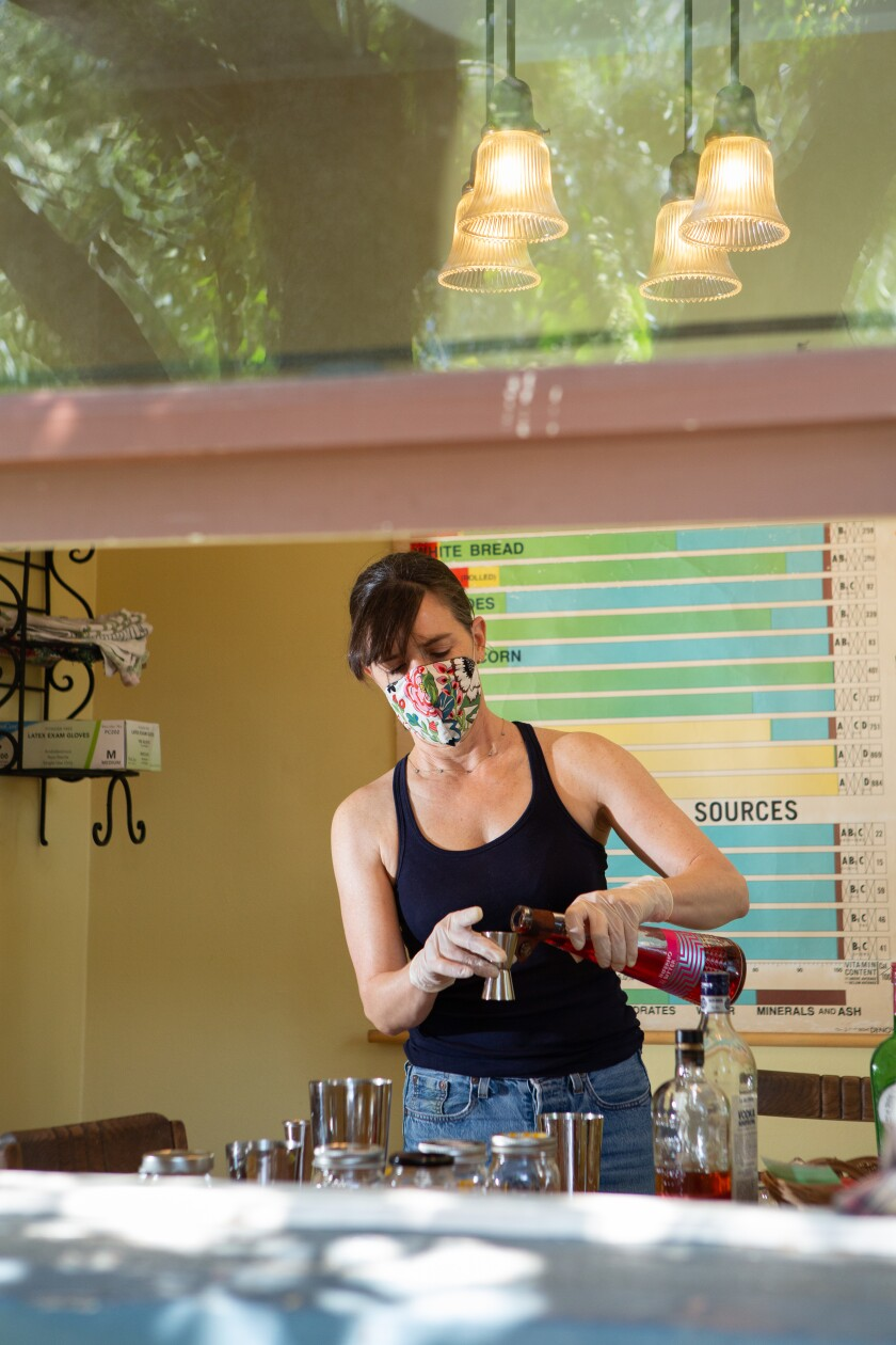 Quinn Cummings mixes vodka Negronis and kiwi whiskey sours, using fruit from a CSA delivery, at her home in Atwater Village.