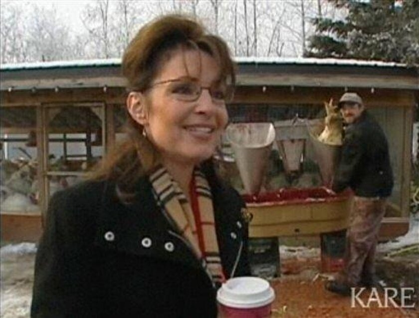 In this image rendered from video and provided by KARE-TV Minneapolis, Alaska Gov. Gov. Sarah Palin speaks during an interview, Thursday, Nov. 20, 2008, at Triple D Farm & Hatchery outside Wasilla, Alaska. As Palin answered questions cameras from the Anchorage Daily News and others showed the bloody work of an employee, right, slaughtering birds behind the former Republican vice presidential candidate. (AP Photo/KARE-TV)