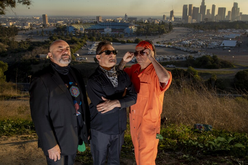 Three men stand in a park  overlooking Dodger Stadium and the L.A. skyline