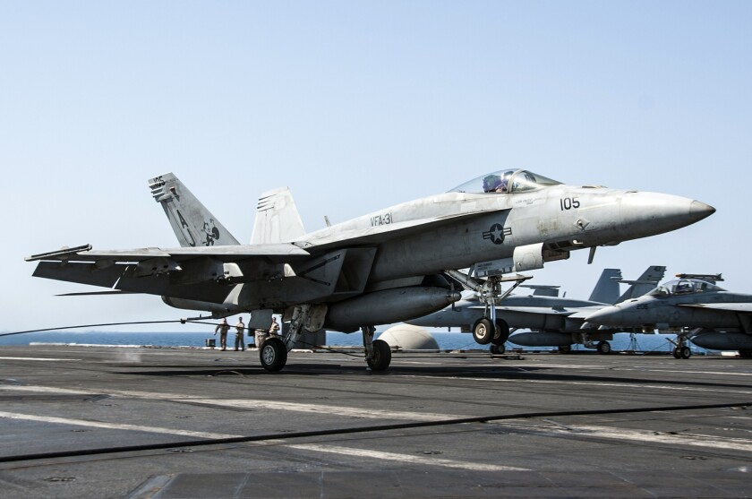 A file photo shows an F/A-18E Super Hornet landing on the aircraft carrier George H.W. Bush after conducting strike missions Sept. 23.