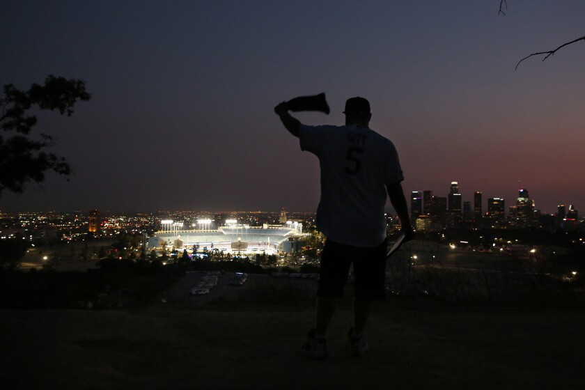 Josh Gitt waves a bandanna while watching the Dodgers play the Milwaukee Brewers from a distance outside Dodger Stadium.