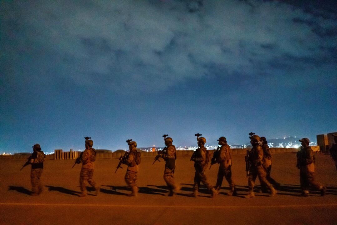 Taliban fighters walk in a line
