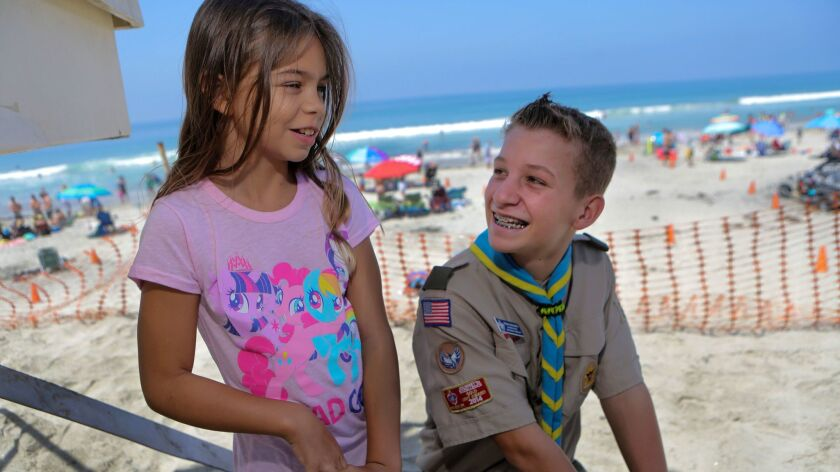 """Jacinda """"JC"""" Marko, 10, with Boy Scout Sean Golding, 13, at Moonlight Beach in Encinitas on Sunday. Golding rescued Marko at the beach on July 10, when she suffered an epileptic seizure in the water."""