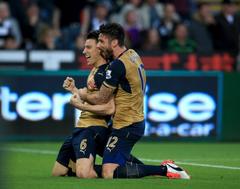 Arsenal's Laurent Koscielny celebrates scoring his side's second goal of the game with teammate Olivier Giroud, right, during their English Premier League soccer match against Swansea at the Liberty Stadium, Swansea, Wales, Saturday, Oct. 31, 2015. (Nick Potts/PA via AP)      UNITED KINGDOM OUT