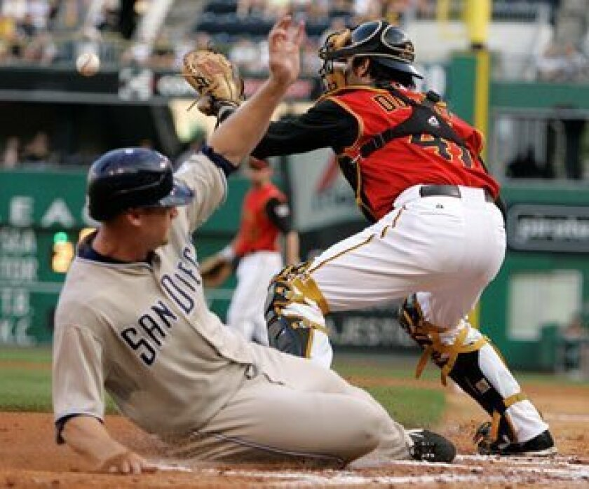 Chase Headley scores on a second-inning single by teammate Josh Bard (not shown) as Pittsburgh Pirates catcher Ryan Doumit waits for the late relay from left fielder Jason Bay in Pittsburgh Friday.