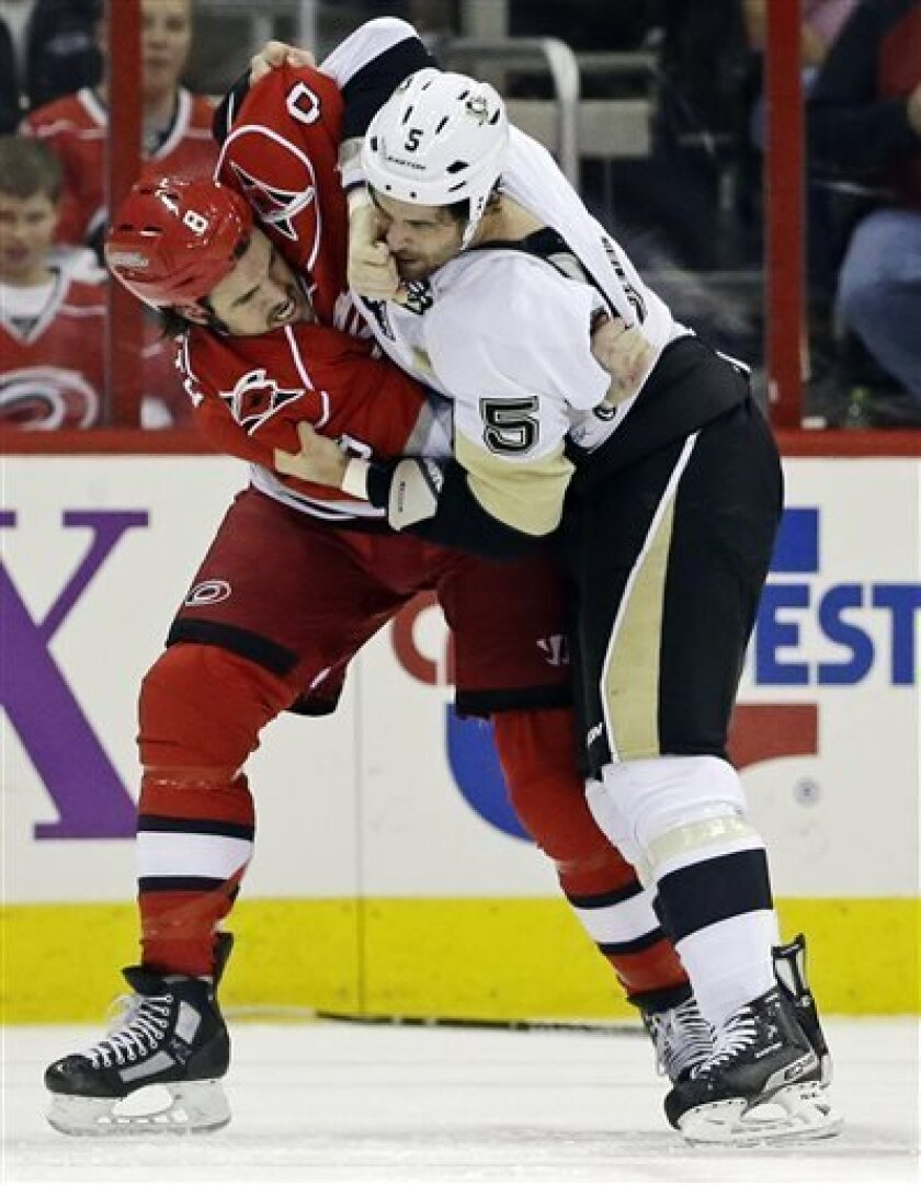 Carolina Hurricanes' Kevin Westgarth (8) and Pittsburgh Penguins' Deryk Engelland (5) fight during the first period of an NHL hockey game in Raleigh, N.C., Tuesday, April 9, 2013. (AP Photo/Gerry Broome)