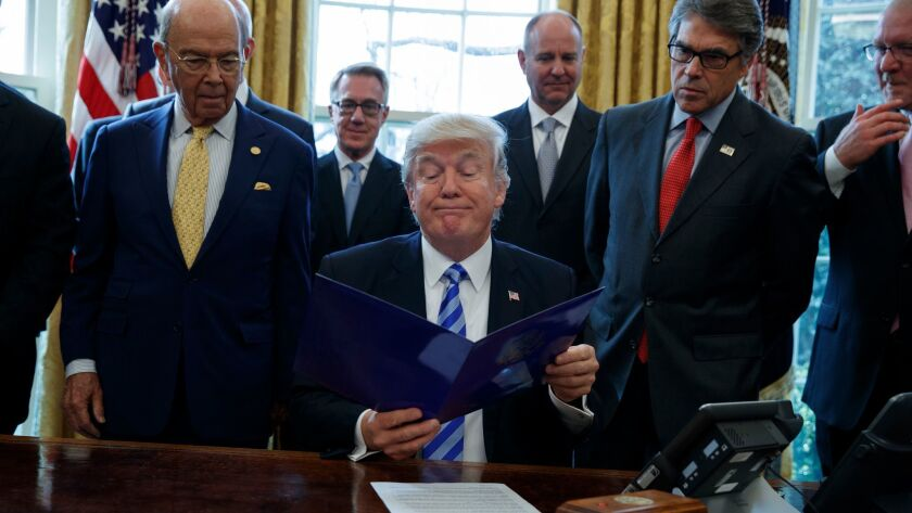 President Trump, flanked by Commerce Secretary Wilbur Ross, left, and Energy Secretary Rick Perry, announces the approval of a permit to build the Keystone XL pipeline, clearing the way for the $8-billion project.