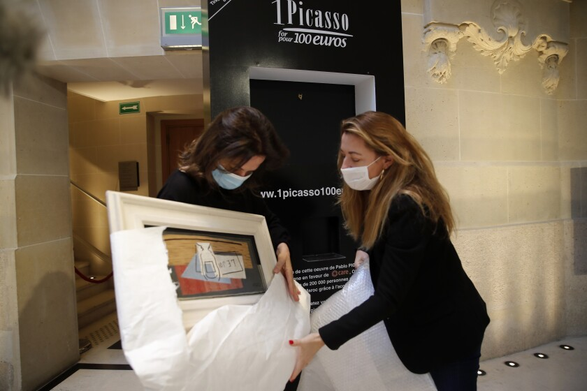 "Raffle organizers Peri Cochin, left, and Arabenne Reille unbox the painting ""Nature Morte"" (Still Life) by Picasso, which was won in the charity draw by an Italian accountant."