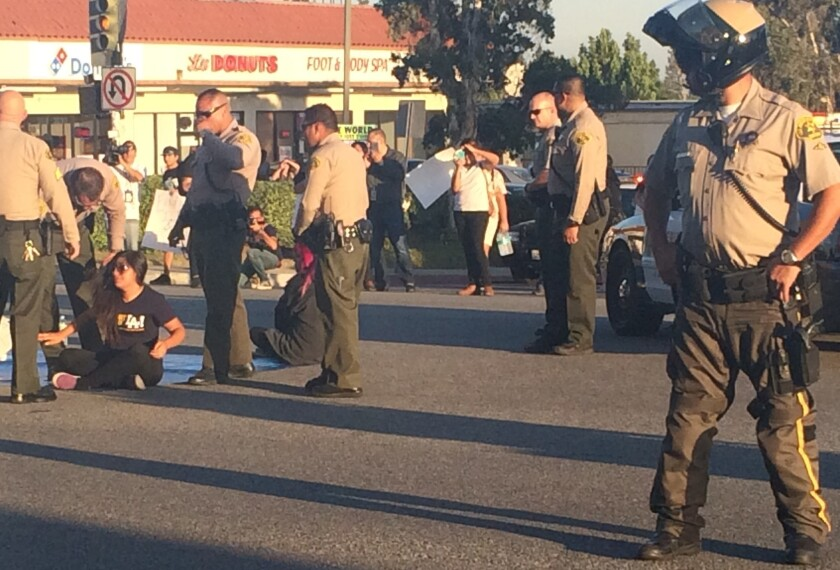Three protesters opposed to Los Angeles County jails collaborating with ICE were arrested Wednesday after they blocked traffic at Highland Avenue and Huntington Drive in Duarte.