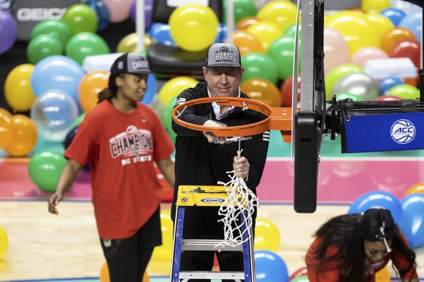 North Carolina State head coach Wes Moore cuts down the net after his team defeated Louisville in the championship of the Atlantic Coast Conference NCAA women's college basketball game in Greensboro, N.C., Sunday, March 7, 2021. (AP Photo/Ben McKeown)