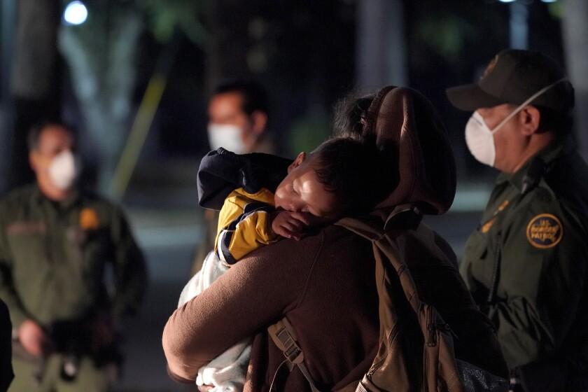 Una migrante con su bebé dormido llega a un centro de detención recepción del servicio de inmigración