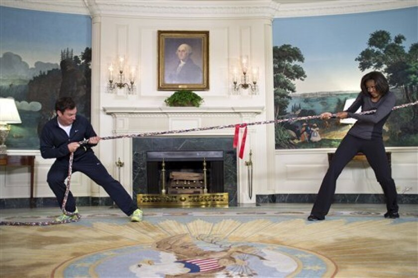 """In this image released by The White House, first lady Michelle Obama participates in a tug of war with television host Jimmy Fallon in the Blue Room of the White House during a taping of """"Late Night with Jimmy Fallon,"""" for the second anniversary of the """"Let's Move!"""" initiative on Jan 25, 2012, at the White House in Washington. The segment is scheduled to air on Tuesday, Feb. 7, 2012. (AP Photo/The White House, Chuck Kennedy)"""