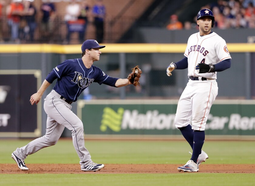 Tampa Bay Rays second baseman Joey Wendle, left, reaches to tag out Houston Astros' George Springer (4), who thought the play was over before the tag, during a game Aug. 27 in Houston.